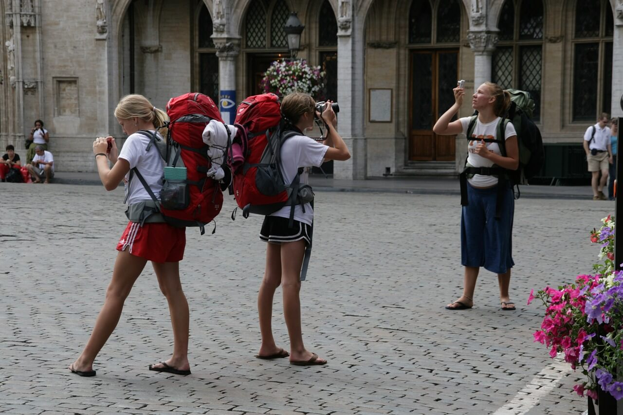 Drei Backpackerinnen fotografieren Sehenswürdigkeiten