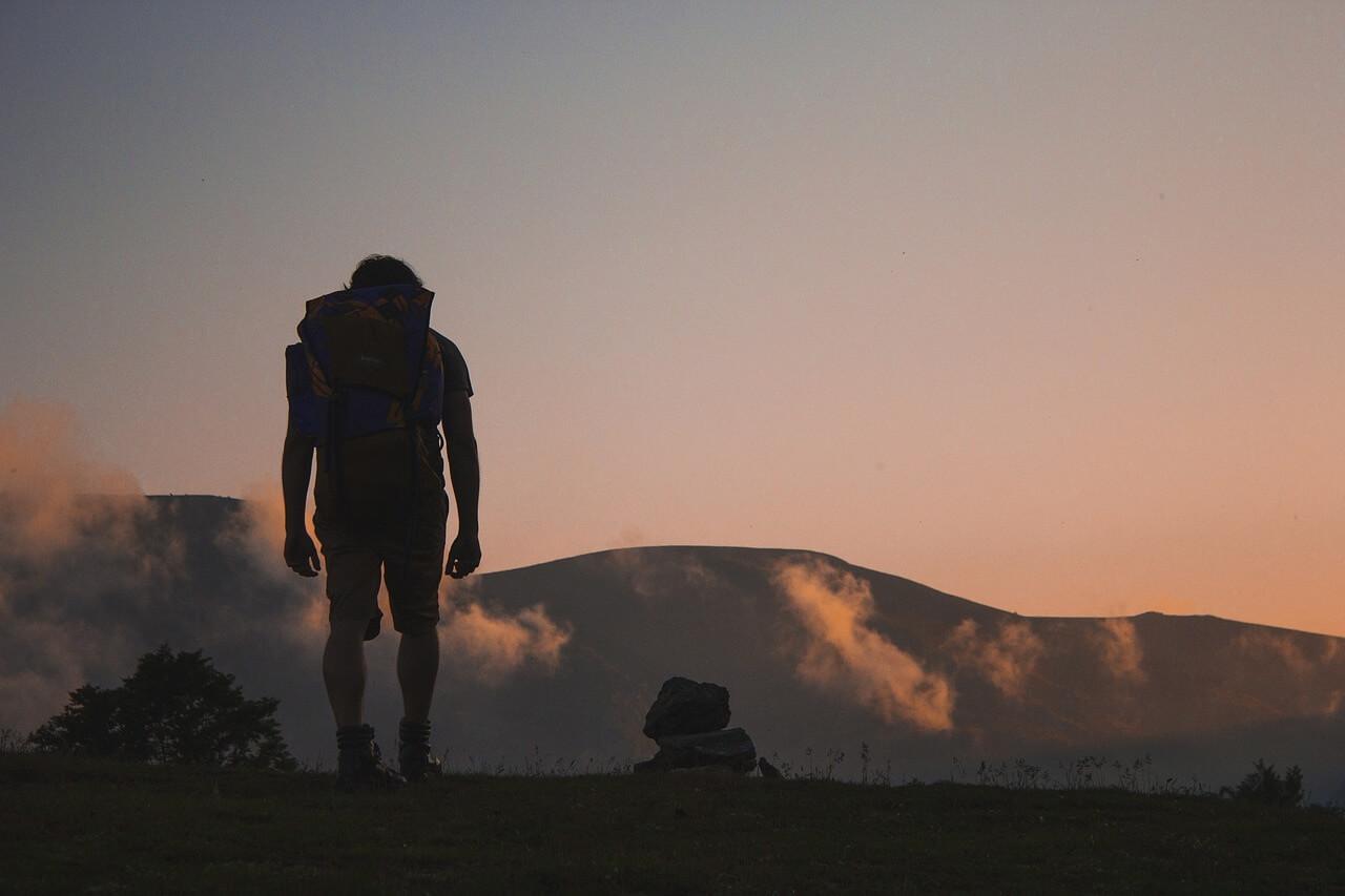 Backpacker schaut auf eine Gebirgslandschaft in der Abenddämmerung