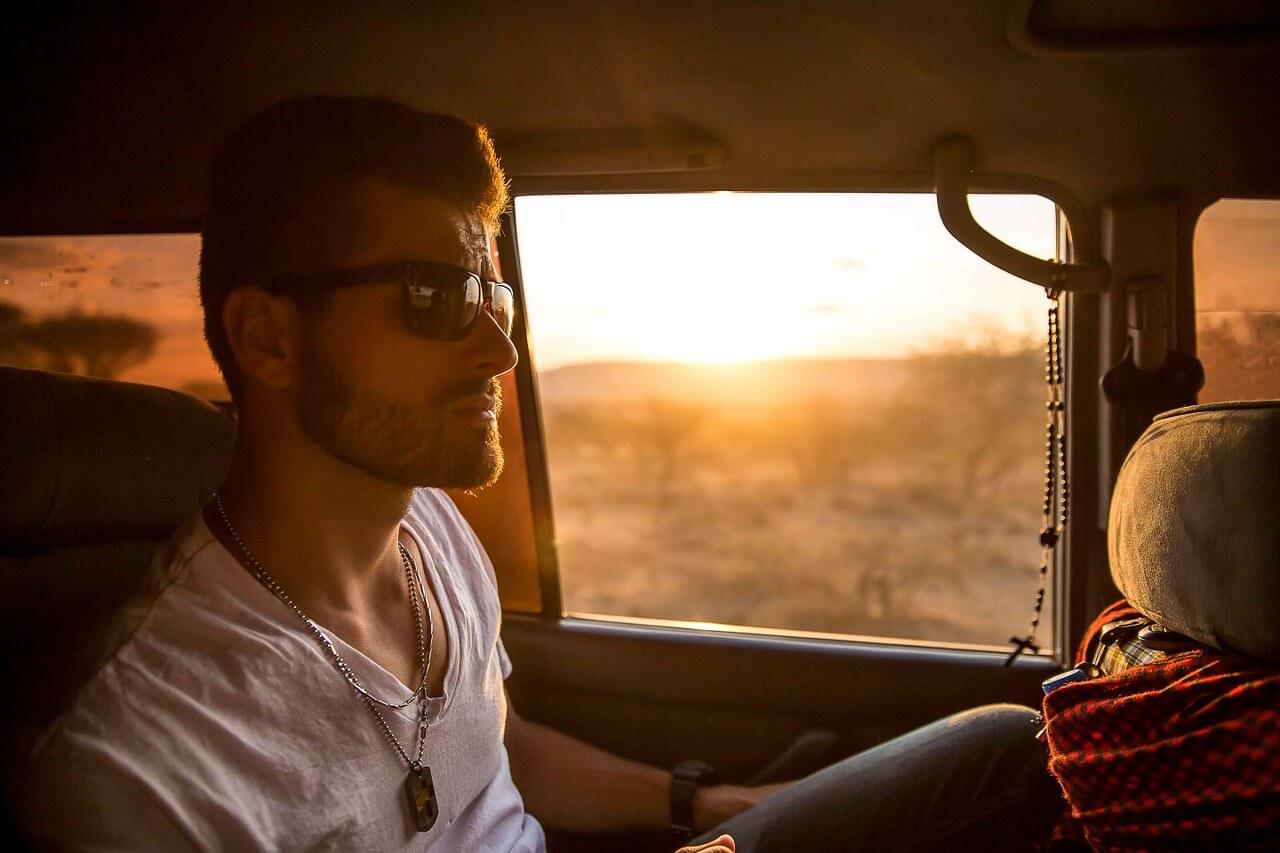 Ein junger Mann sitzt in einem Auto während die Sonne untergeht