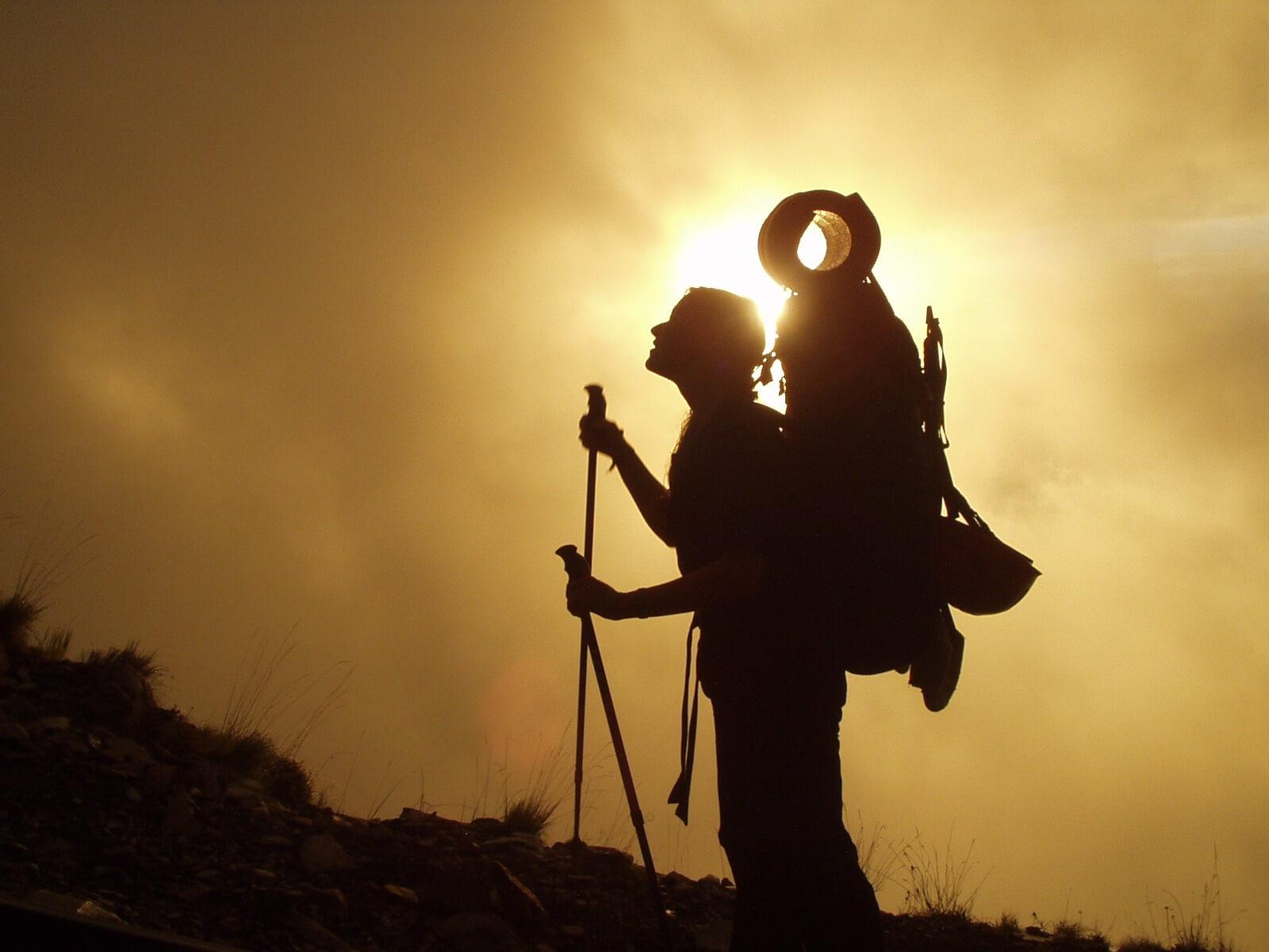 Eine Wanderin steht mit großem Backpack vor Nebel