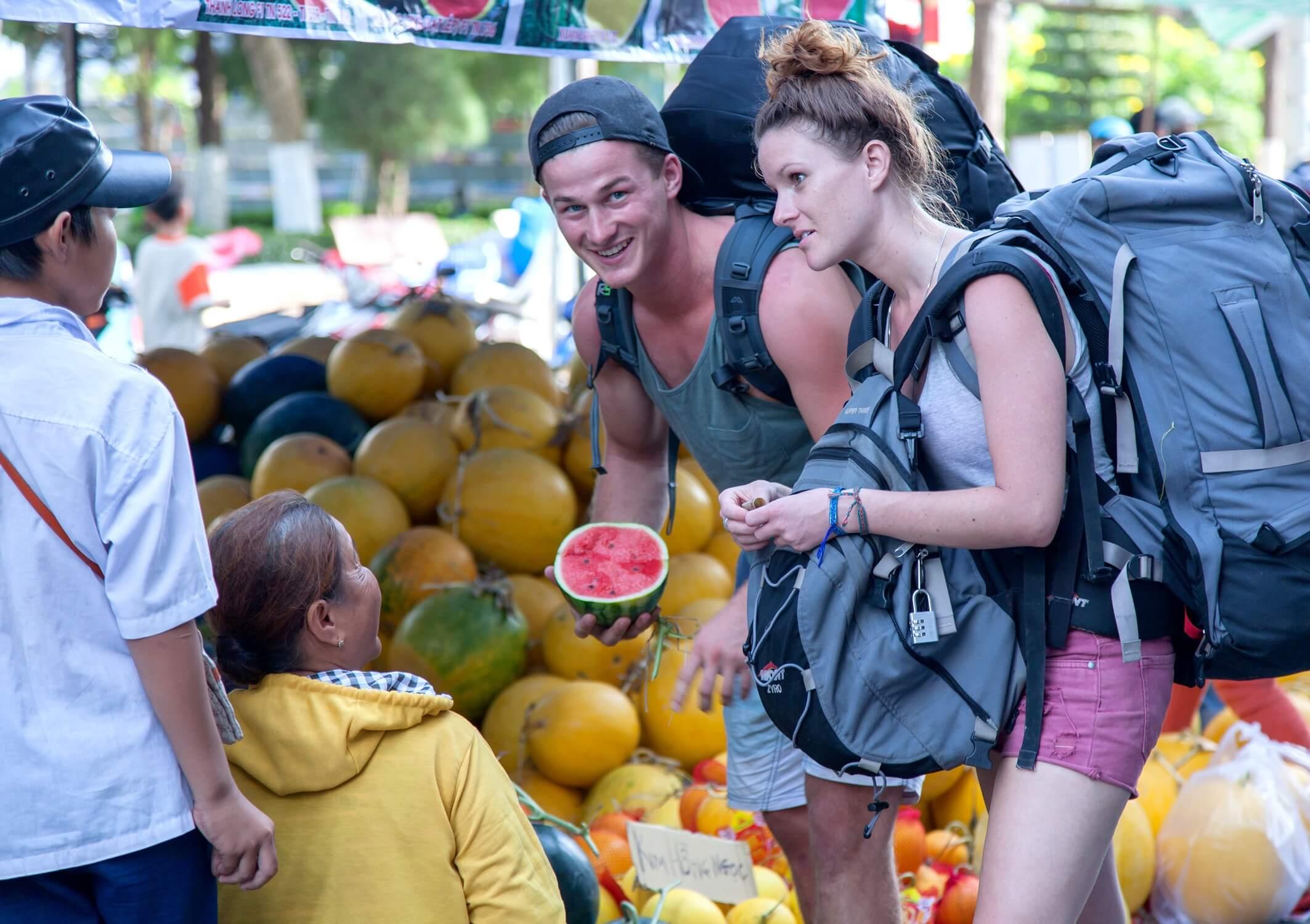 Beim Auslandsjahr nach dem Abi: Backpacker verhandeln mit Einheimischen um Obst