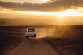 Ein Auto fährt während des Sonnenuntergangs durchs Outback