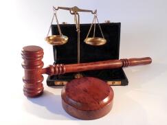 Ein hölzerner Richterhammer liegt vor einer Goldwaage