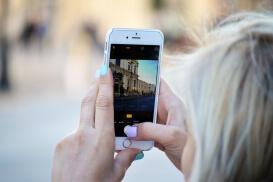 Frau fotografiert Kulisse mit ihrem iPhone