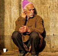 Ein armer, alter Australier hockt vor einer Wand