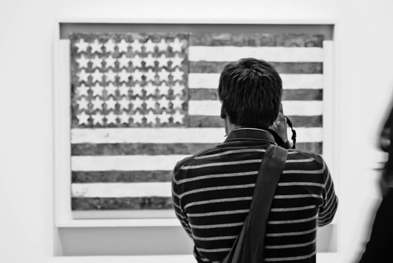 Mann vor einer Amerikanische Flagge in einem Kunstmuseum