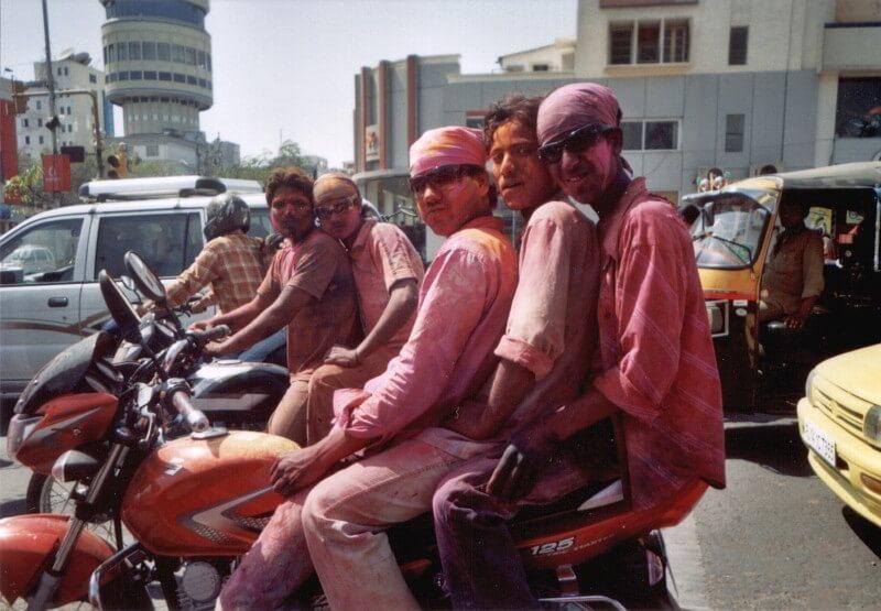 Drei Männer auf einem Moped beim Holi