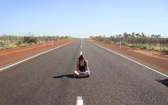 Jenny sitzt lesend auf einer endlosen Straße