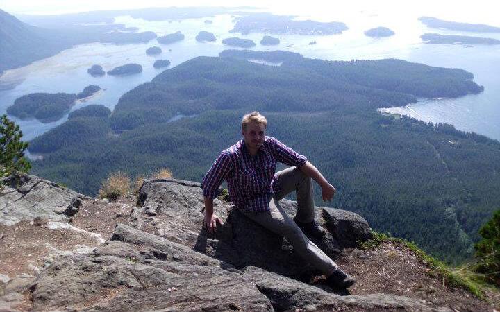 Andreas auf einem Berg vor einer See-Wald-Landschaft