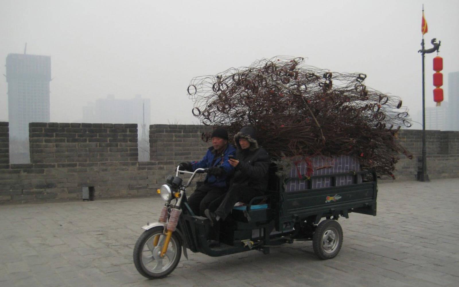 Zwei Chinesen fahren auf einem Lasten-Tuk-Tuk