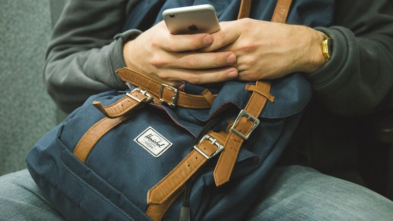 Mann mit Handy im Zug