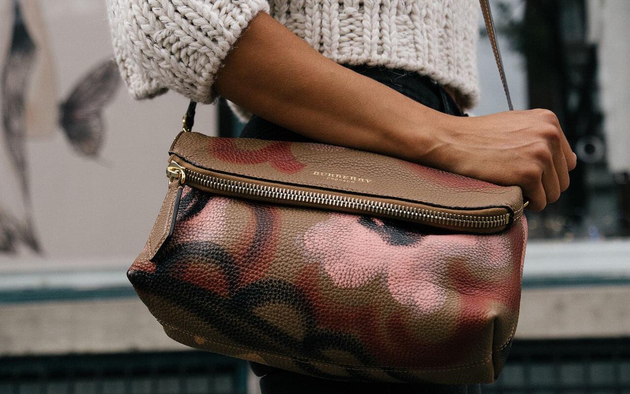 Frau mit ihrer Hand an ihrer Handtasche