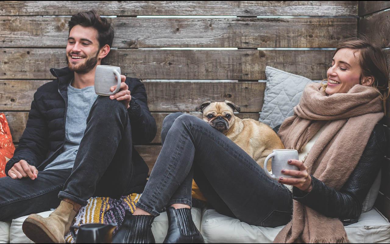 Pärchen mit Hund bei einem kleinen Picknick