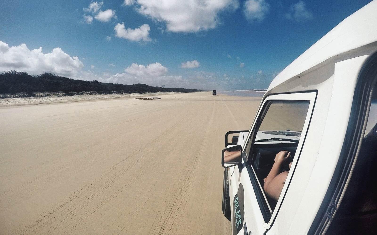 Blick aus dem fahrenden Auto über den Strand