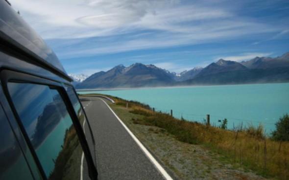 Vorbeifahrt an einem grünen Gebirgssee