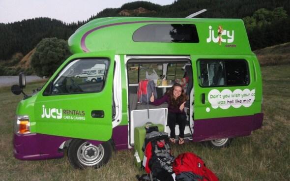 Backpackerin vor ihrem Campervan