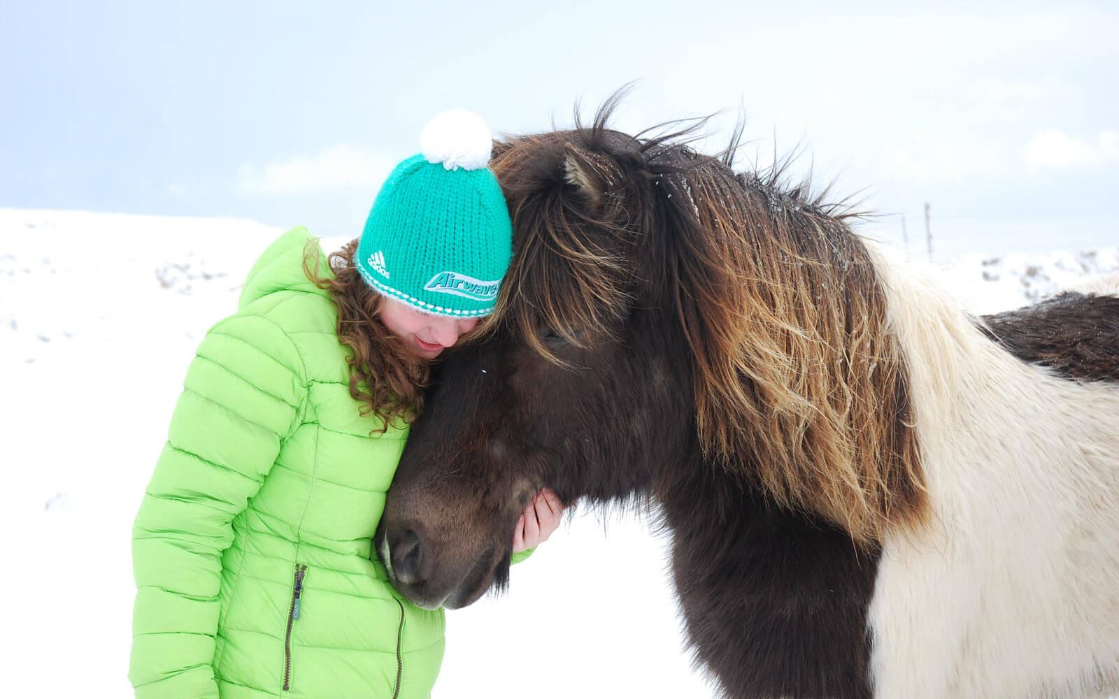 Farmhelferin Isabelle mit einem Island-Pferd im Schnee