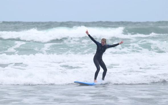 Annie surft in Raglan, Neuseeland