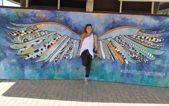 Austauschschülerin Myrna vor dem #lovedowntowntauranga-Bild in Tauranga