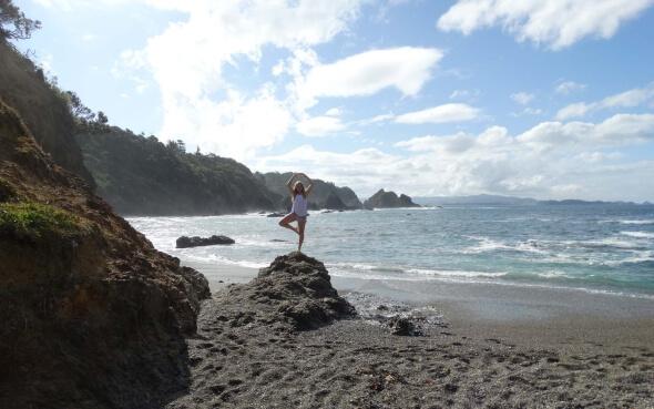 Austauschschülerin Myrna in Yoga Pose am Strand in Neuseeland