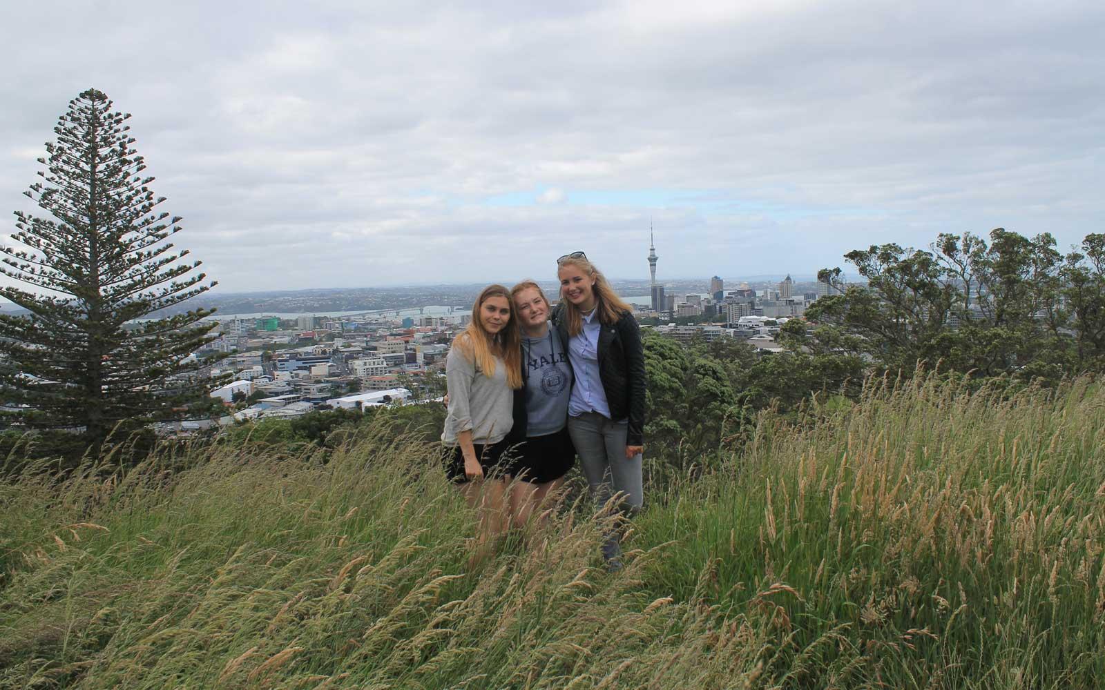 Austauschschülerin Myrna mit zwei Freundinnen am Mount Eden vor der Skyline Aucklands