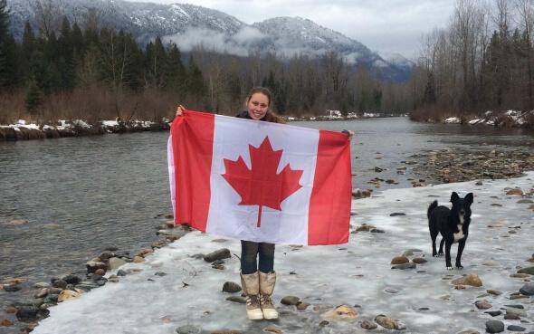 Vanessa mit Kanadaflagge und Hund vor Schneelandschaft