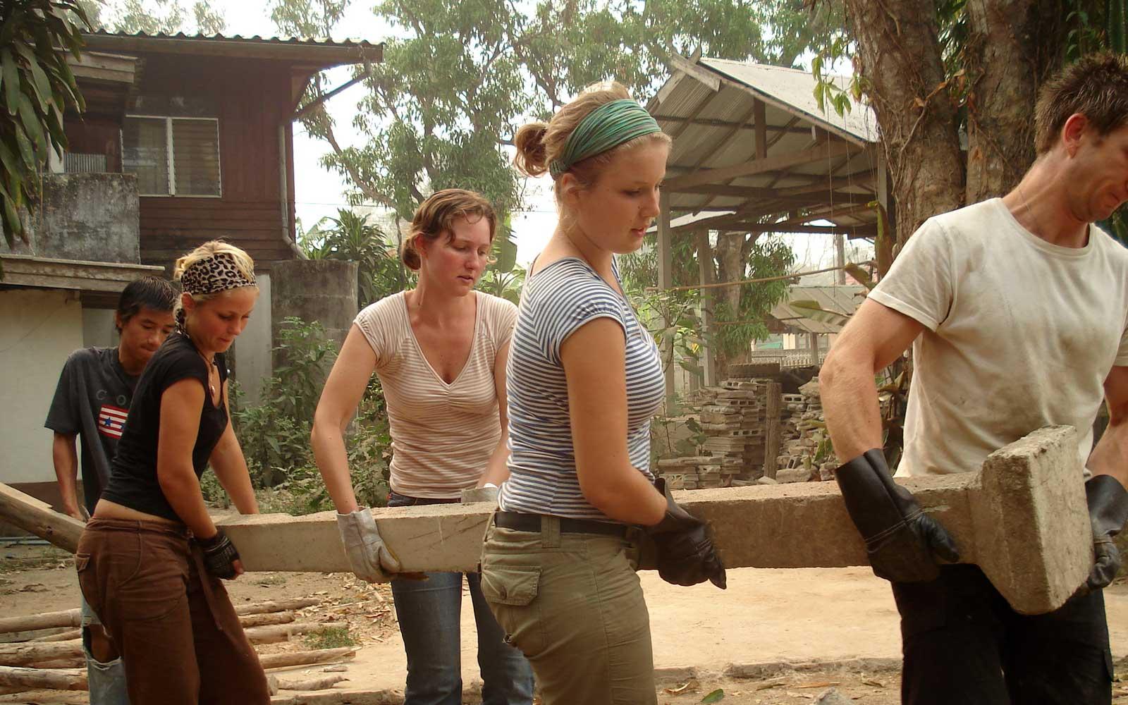 Junge Leute tragen Holzbalken für den Hüttenbau