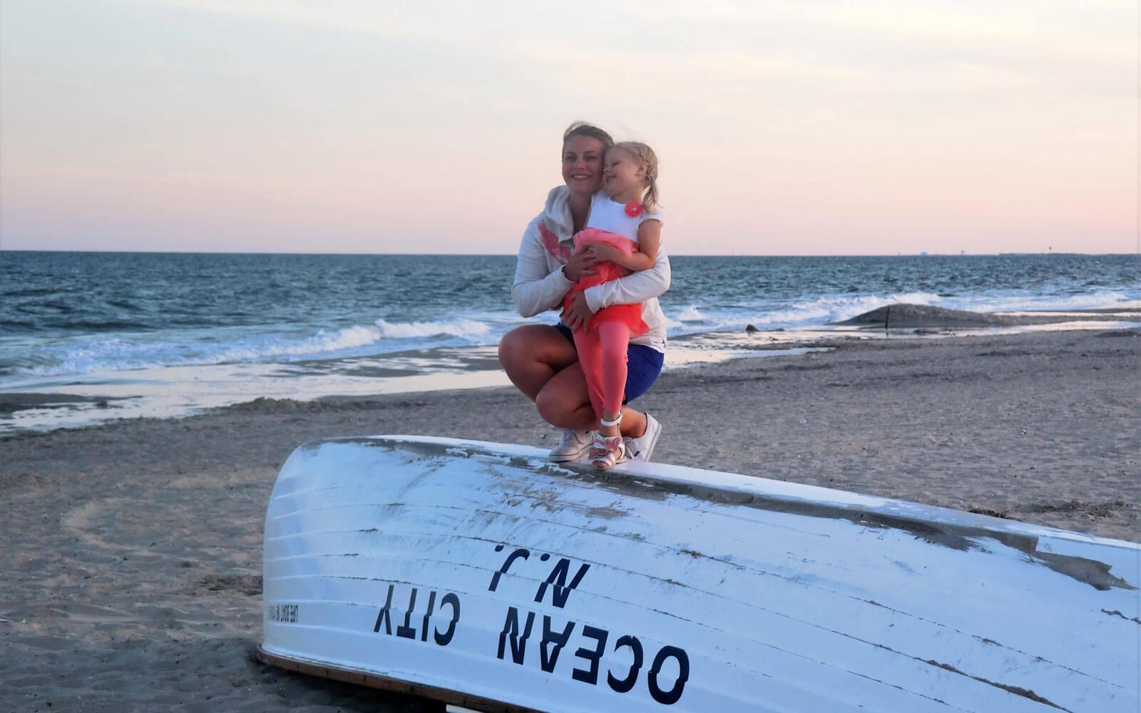 Au-pair mit Kind schauen auf das Meer