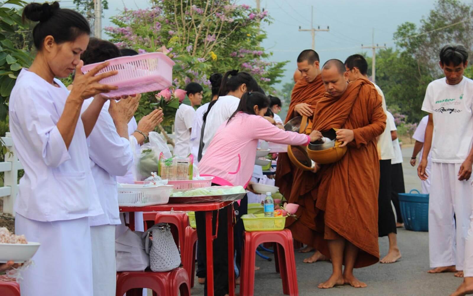 Almosen verteilen für Mönche in Thailand