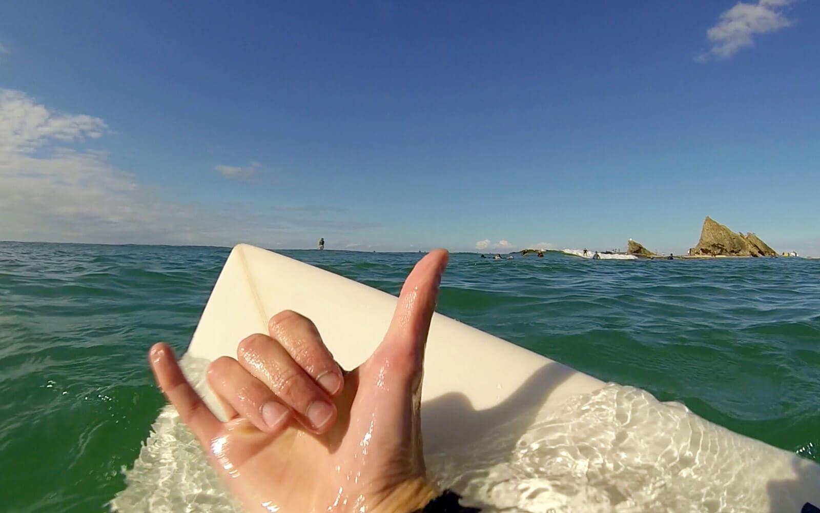 Surfboard und Hang Loose-Zeichen in Australien