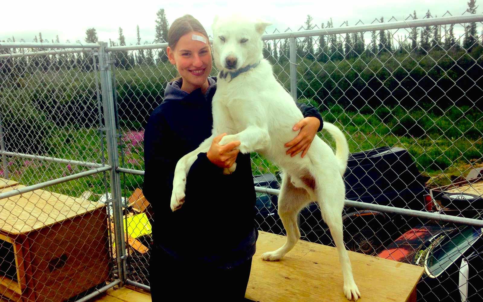 Anja kuschelt mit weißem Husky