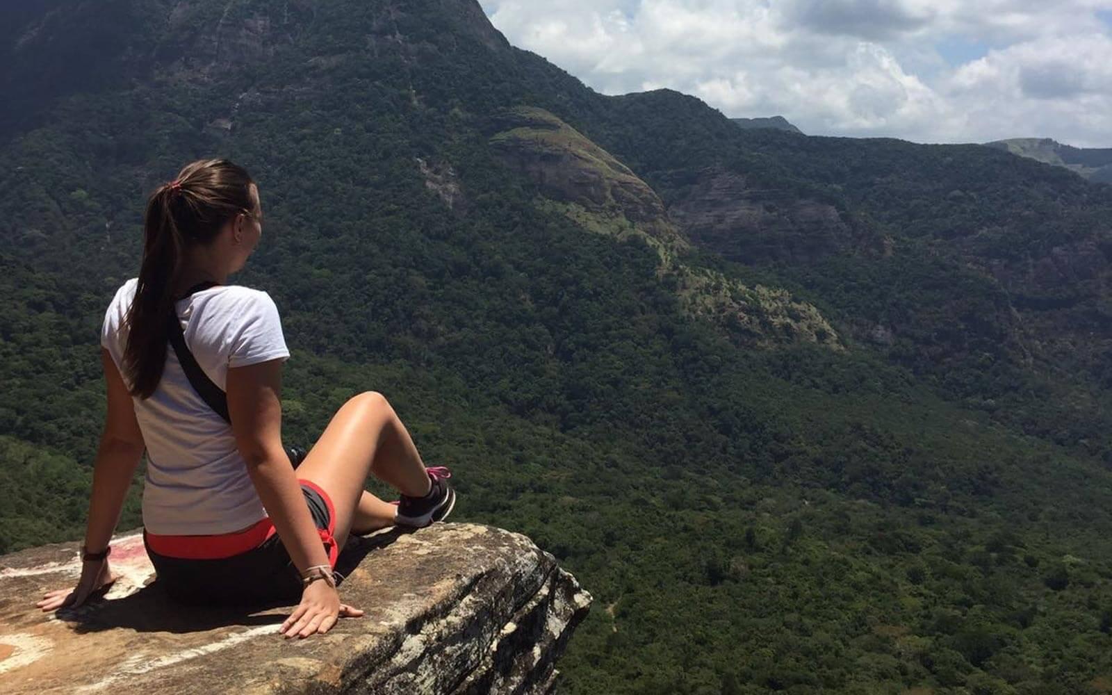 Vivien sitzt auf einem Felsvorsprung und blickt in die grüne, hügelige Landschaft