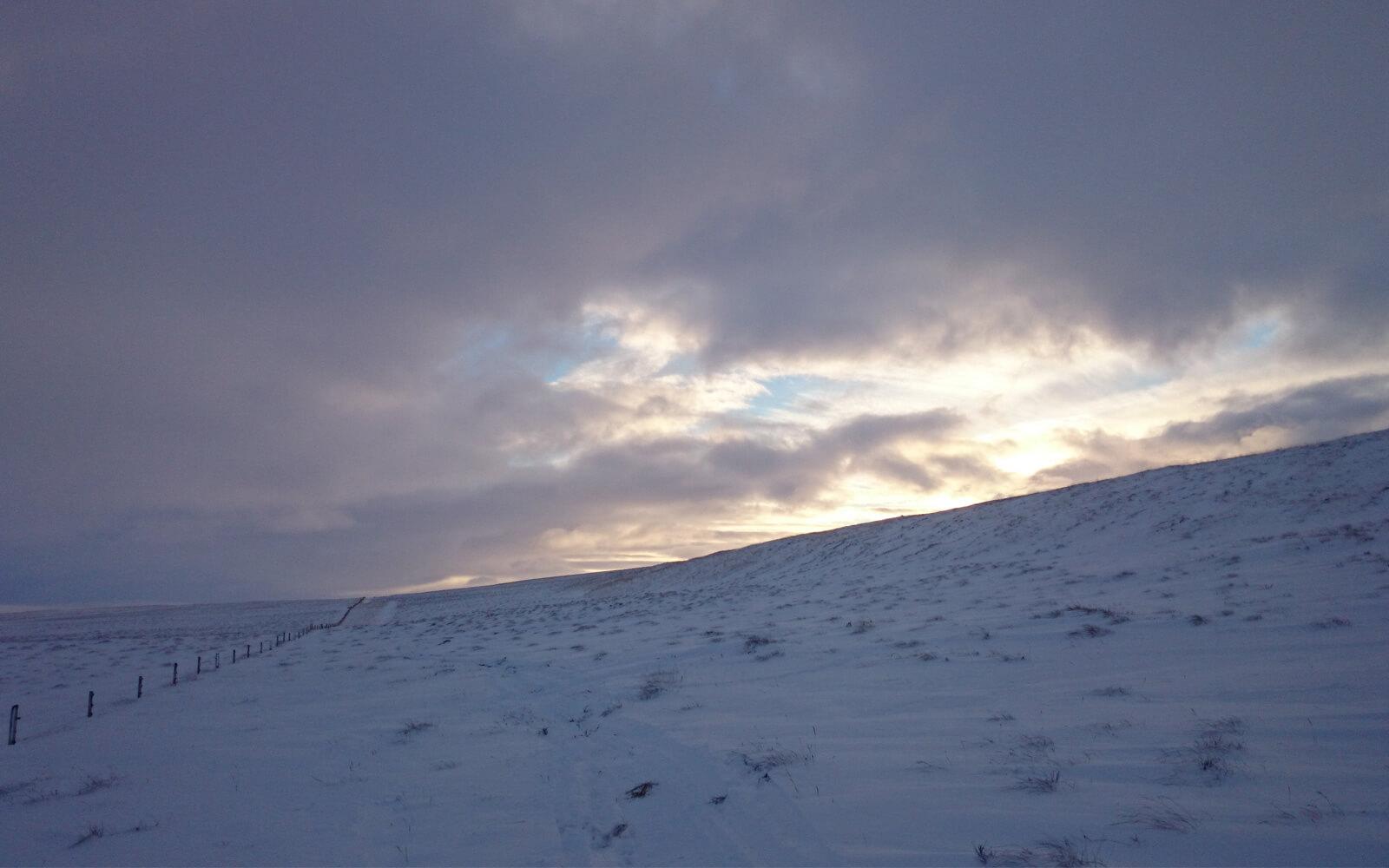 Schneebedeckte Weiden unter dunklen Wolken