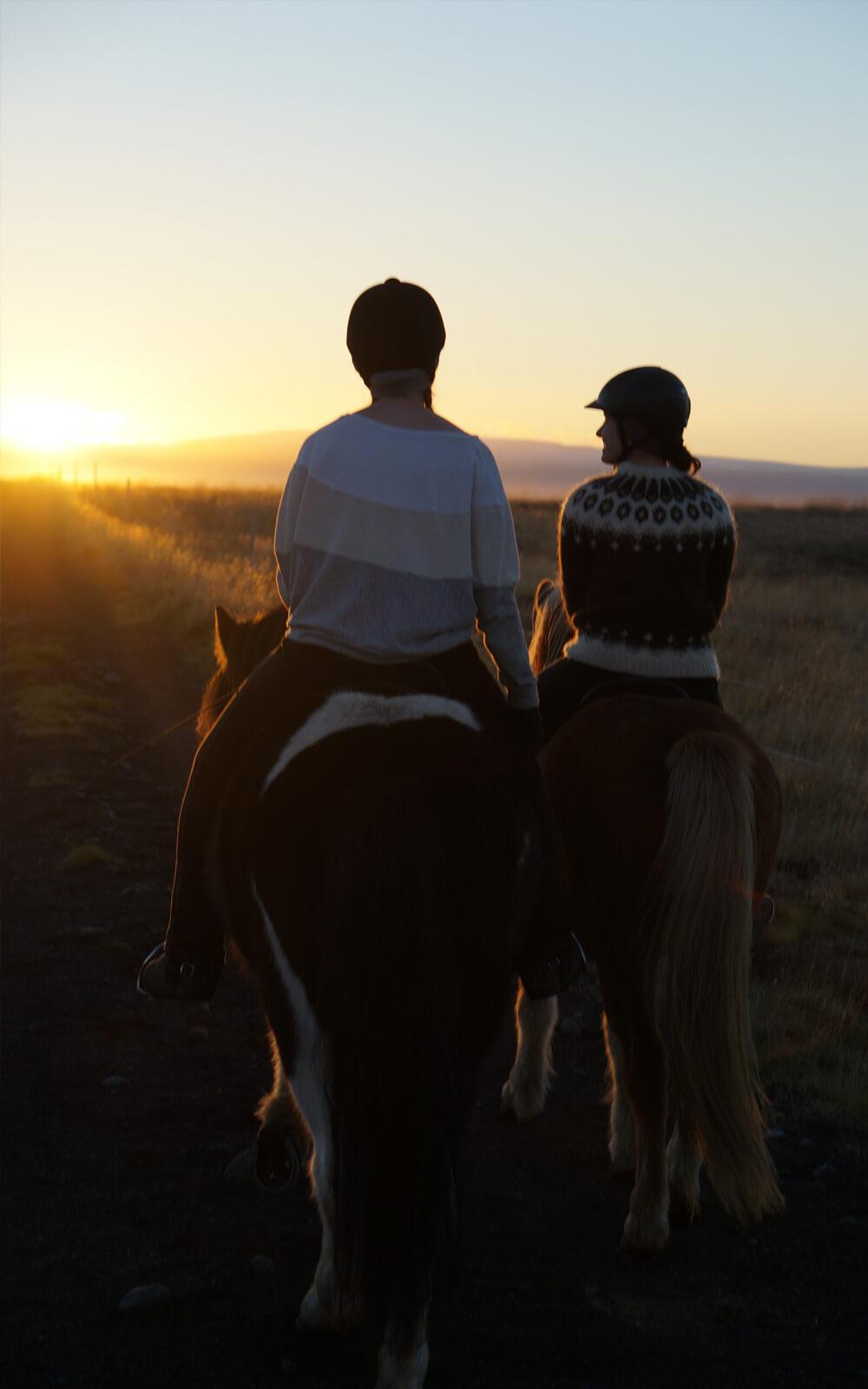Zwei Reiter von hinten in Richtung Sonnenuntergang reitend