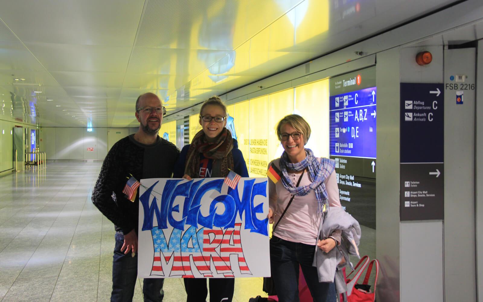Mara mit ihren Eltern am Flughafen mit »Welcome Mara« Schild