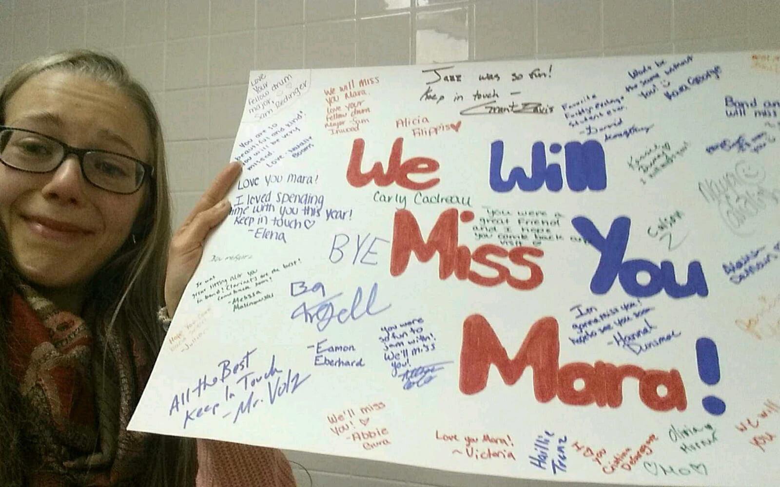 Mara zeigt ein Plakat mit »We will miss you Mara« und vielen Unterschriften und Grüßen