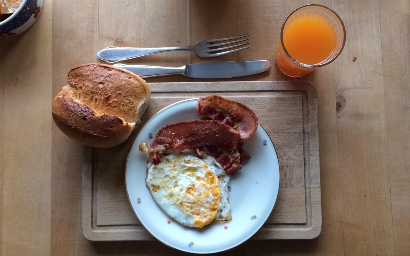 Frühstücksteller mit Brötchen, Spiegeleiern und Speck
