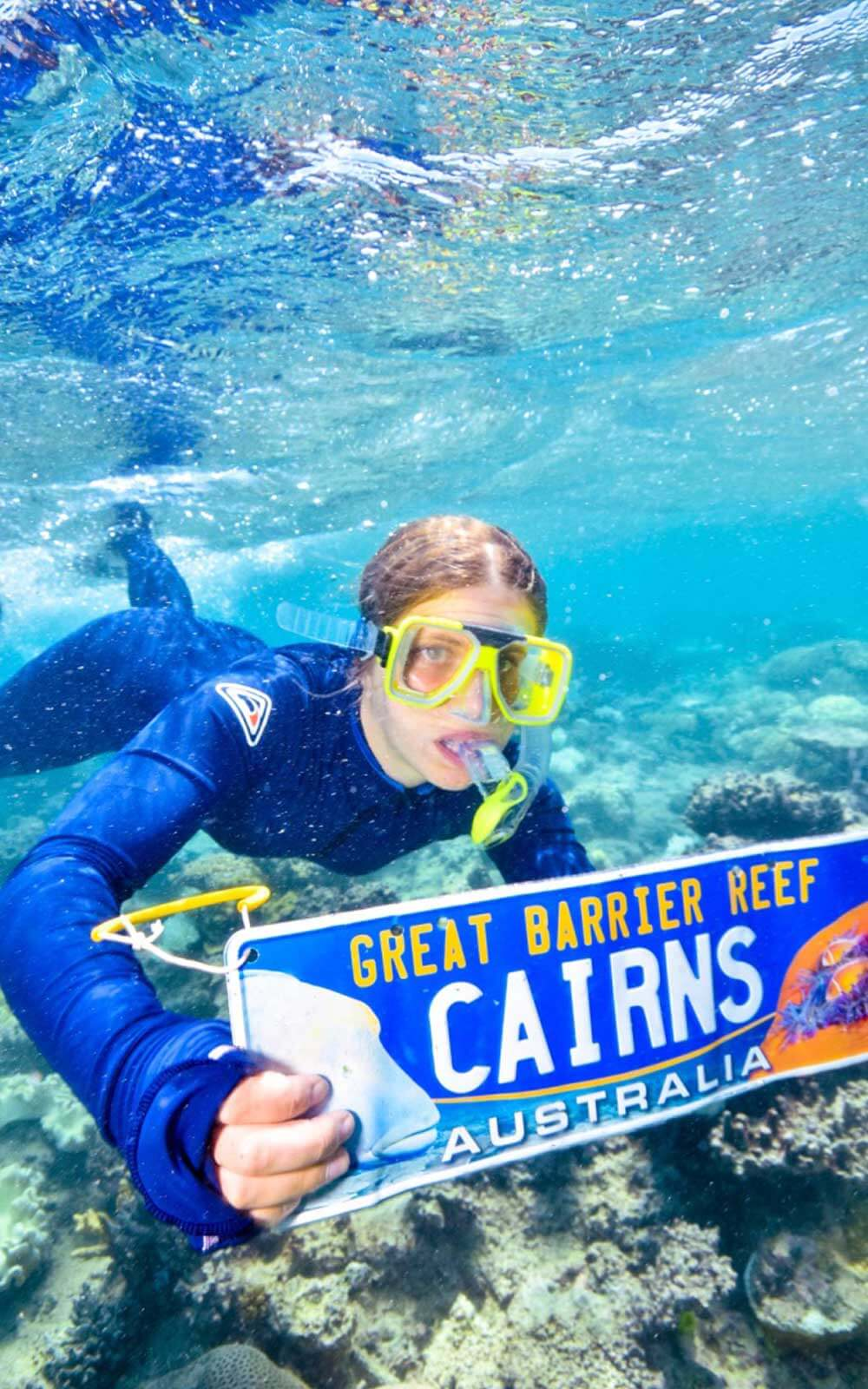 Lena schnorchelnd unter Wasser mit Cairns-Schild in der Hand