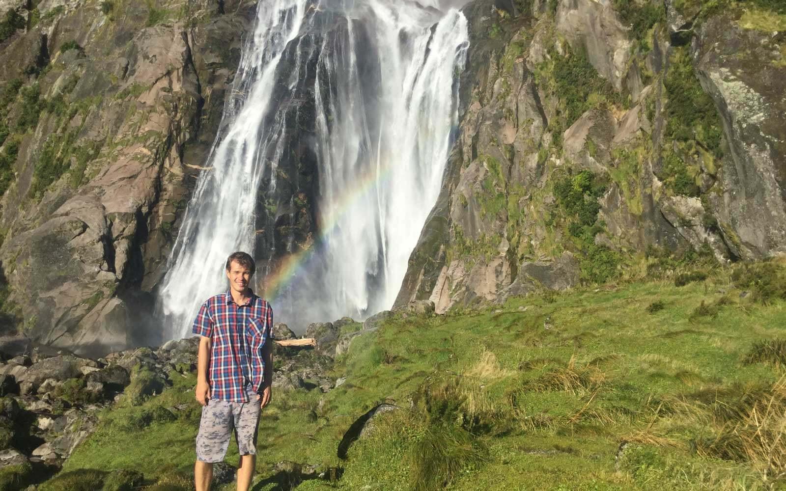 Justin vor Wasserfall mit Regenbogen