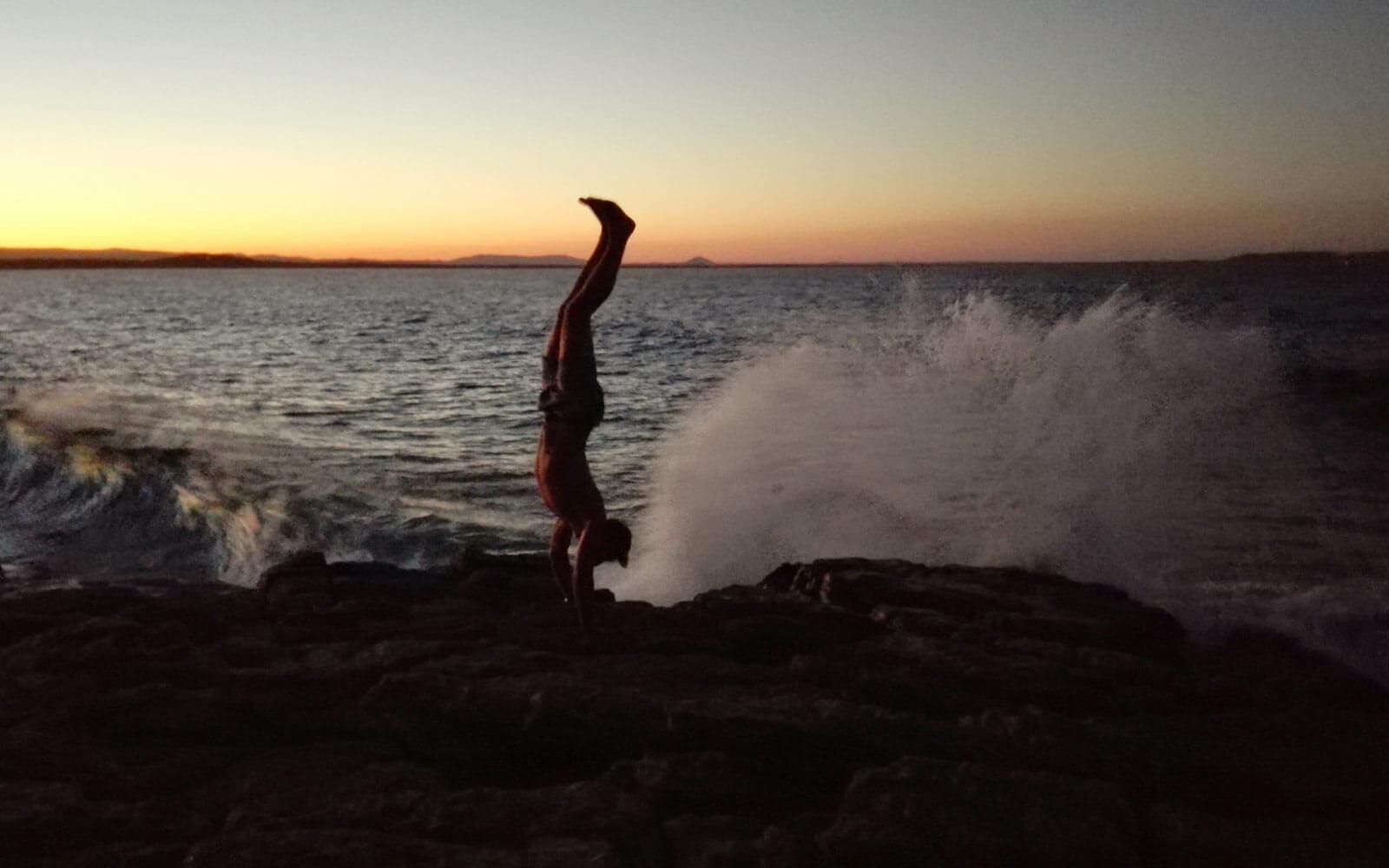 Paul macht einen Handstand am Strand