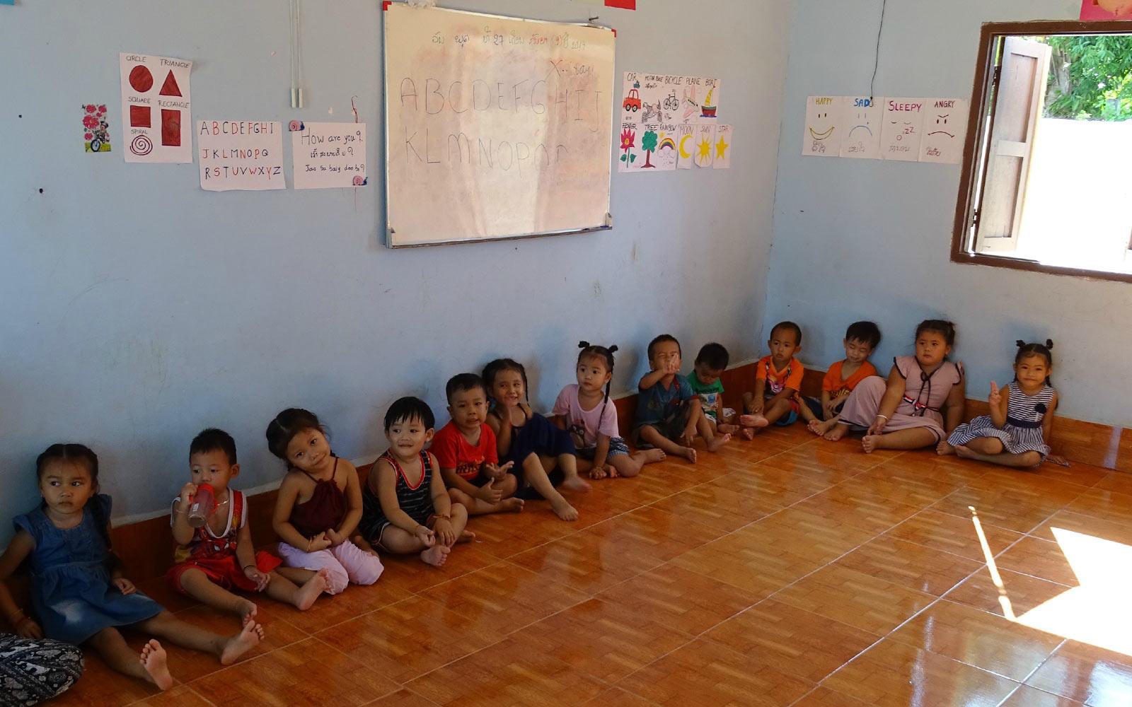 Kinder sitzen an einer Wand entlang auf dem Boden