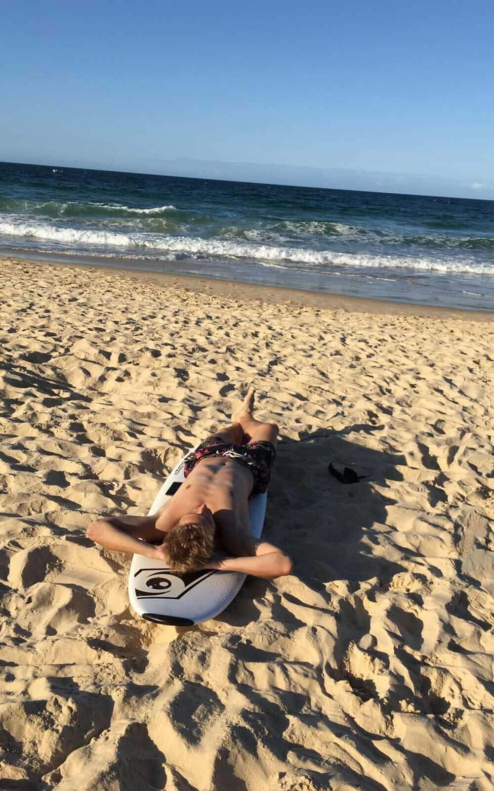 Paul lliegt am Strand auf seinem Surfbrett