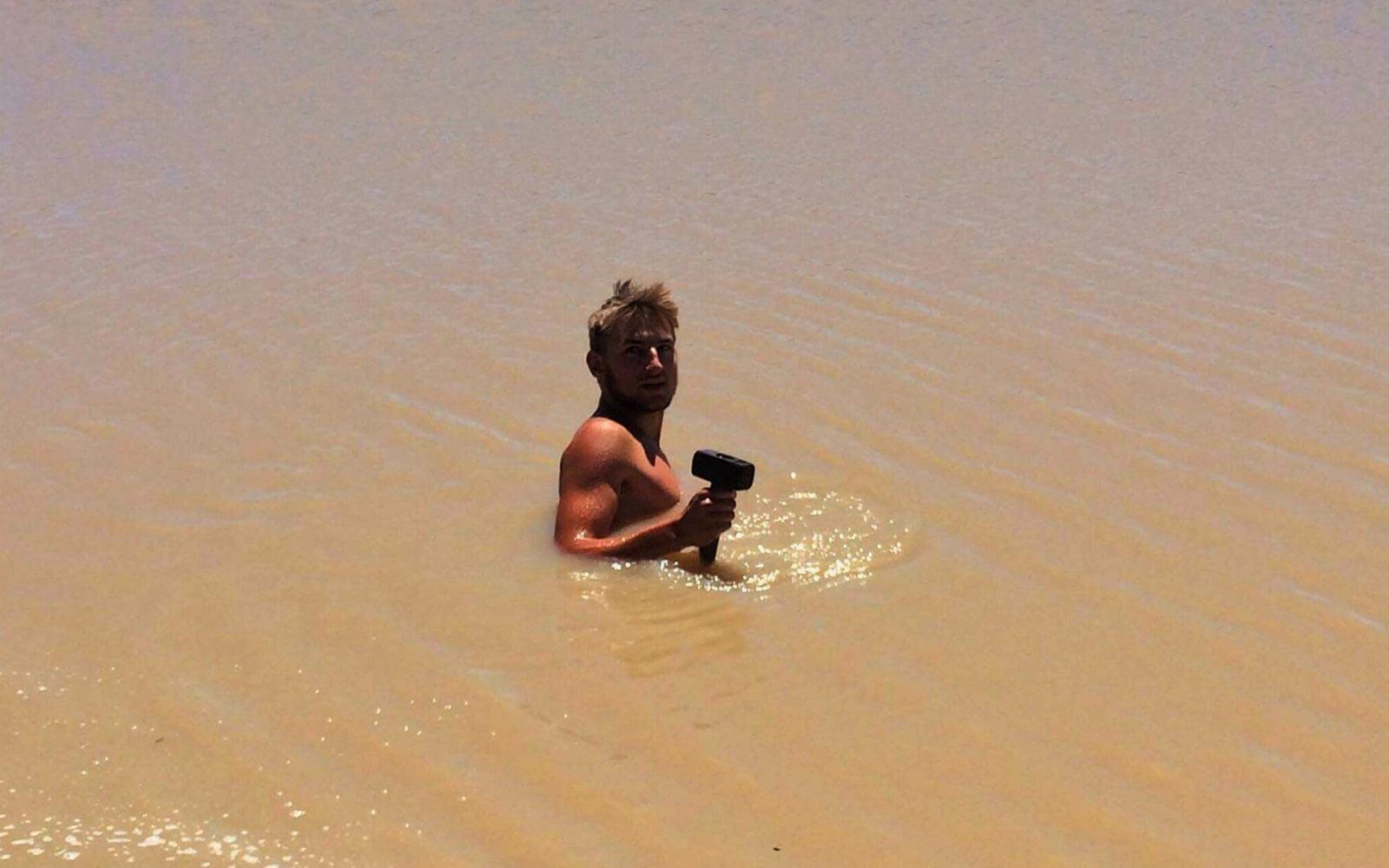 Paul mit einem Hammer in der Hand im Wasser