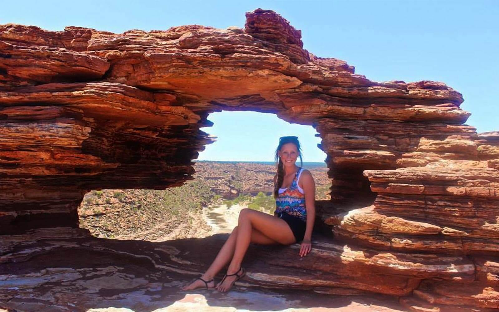 Jana posiert vor einem roten Felsen