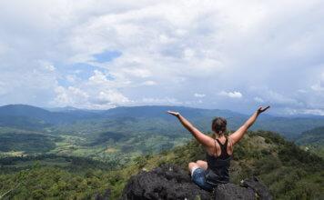 Mädchen sitzt auf einem Felsen und genießt die Aussicht