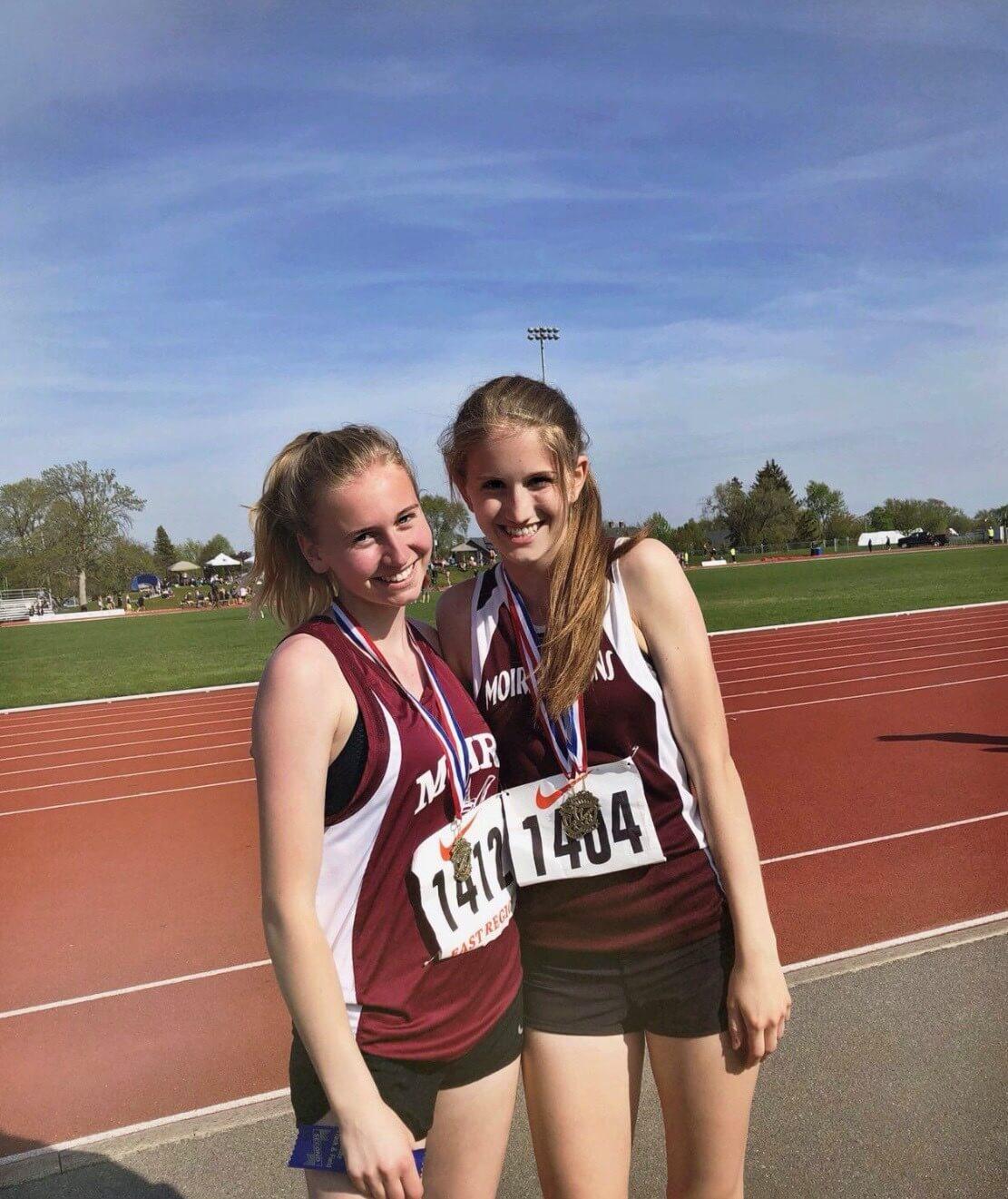 Zwei Mädels in Sportoufit mit Medaillen um den Hals