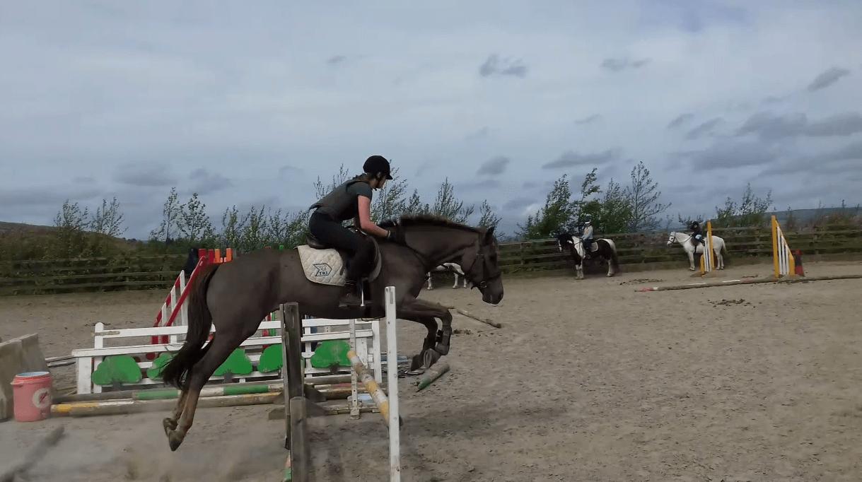 Leonie springt mit Pferd über Hindernis