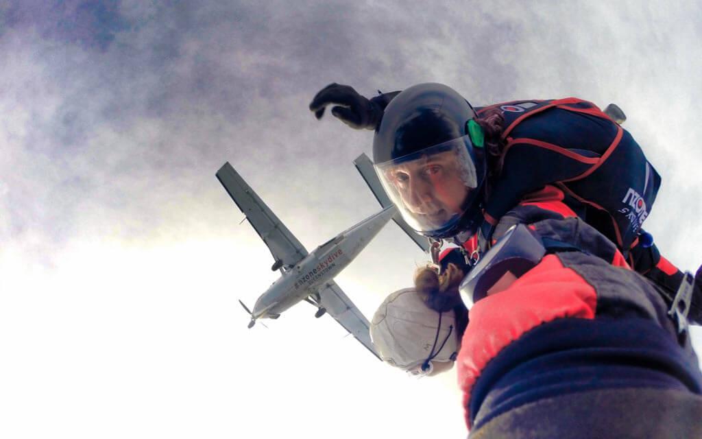 Tandemsprung mit Blick von unten nach oben in das Gesicht des Sprunglehrers inkl. Flugzeug