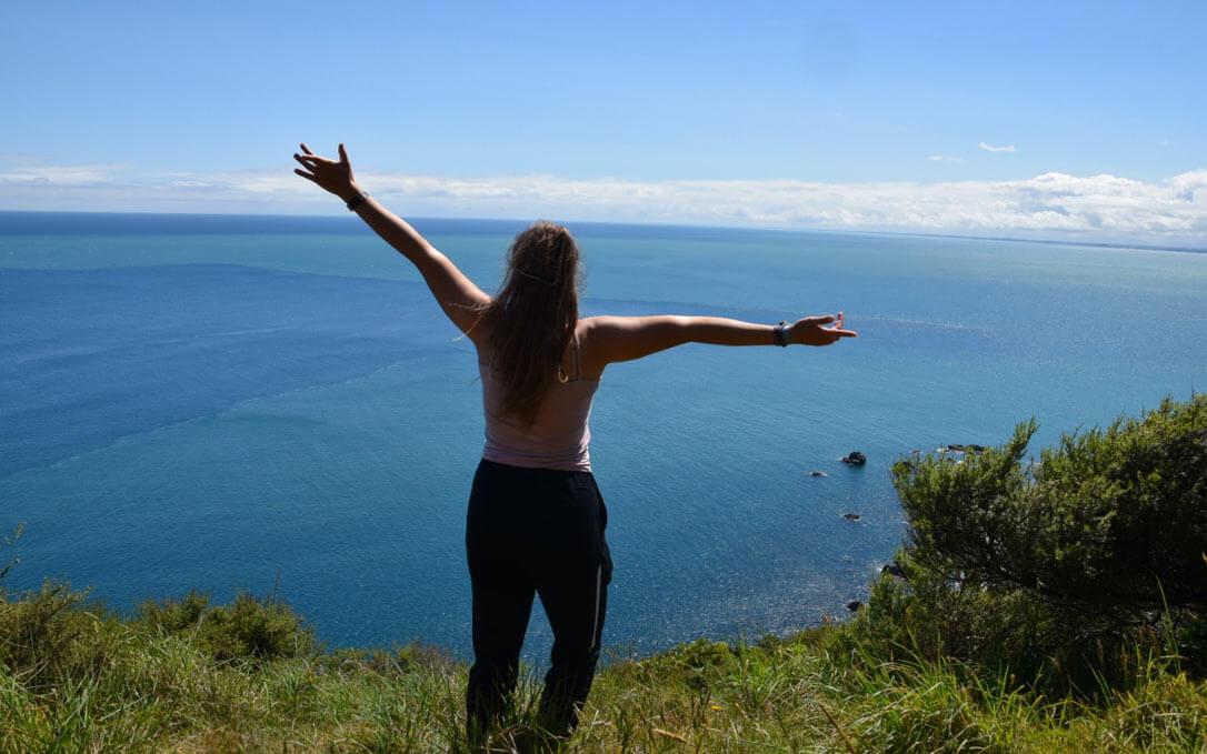 Schüleraustausch Neuseland: Mädchen von hinten mit ausgebreiteten Armen und dem Blick auf den endlosen Ozean