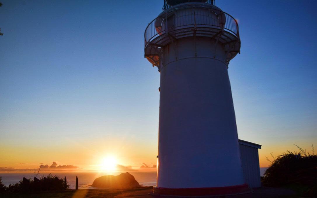 Sonnenaufgang hinter dem East Cape Leuchtturm an der neuseeländischen Ostküste (Nordinsel)
